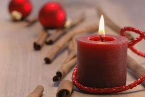 Christmas decoration with burning candle and cinnamon sticks